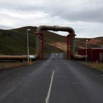 Pipes carrying geothermally heated water across the road at Krafla, Iceland